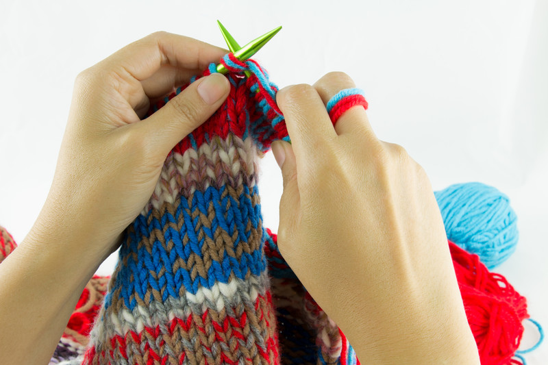 holding knitting needles to knit a row